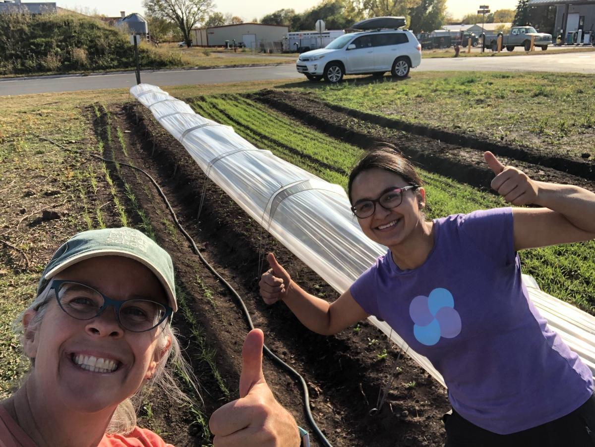 Julie and Gaby smiling with their thumbs up in front of a row of crops covered with sheer row cover