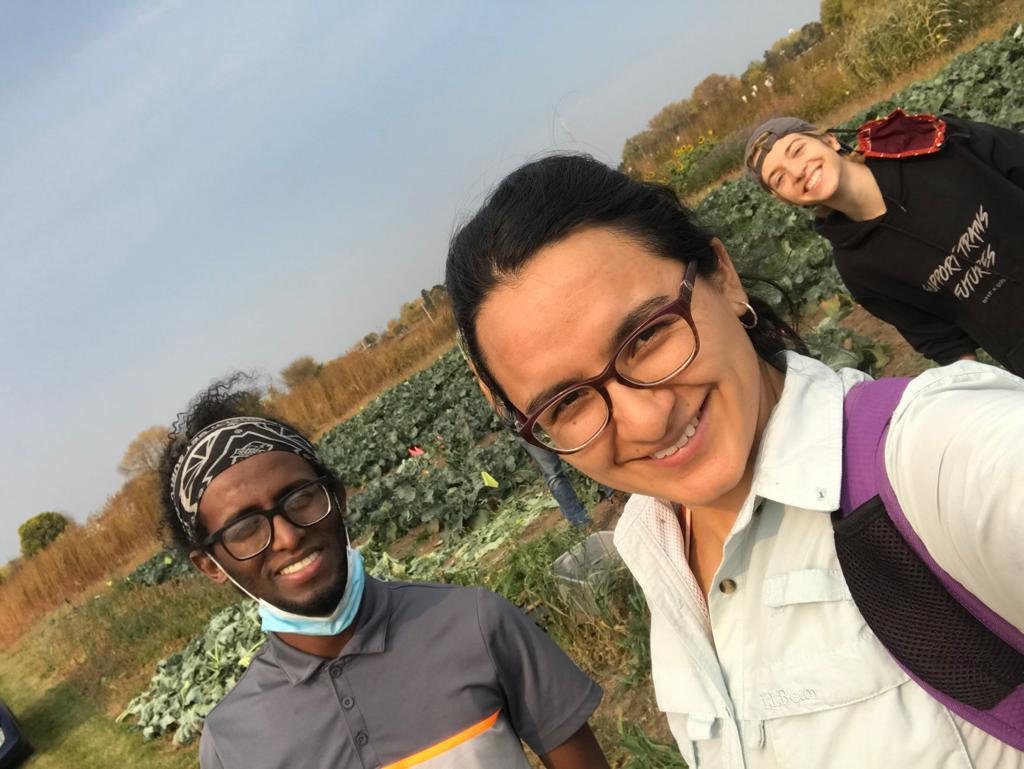 Bonsa, Gaby, and Madi stand and smile in front of the summer cover crops plots in St. Paul